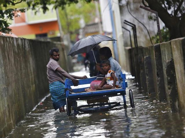 A man carries his family on a rickshaw cart as he wades through a flooded street in Chennai.