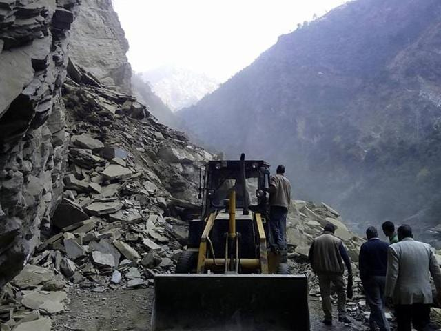 PWD  workers  clearing debris after  massive landslide blocked the Chandigarh-Manali national highway.