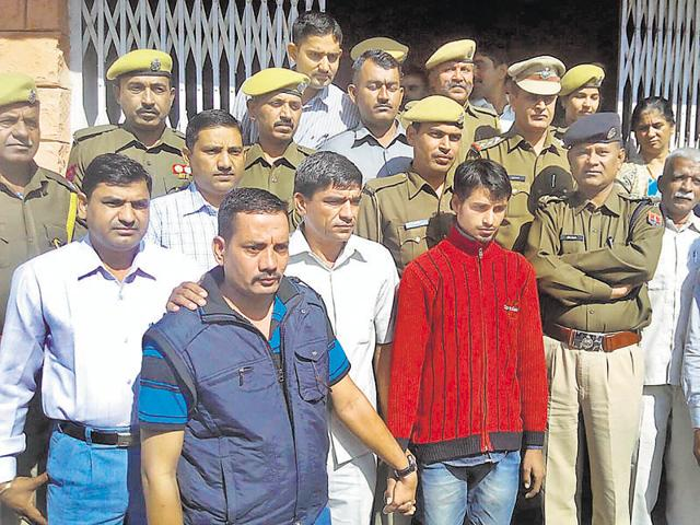 Police with Rahul whom they claim killed his cousin Ajay Valmiki, in Barmer on Saturday.