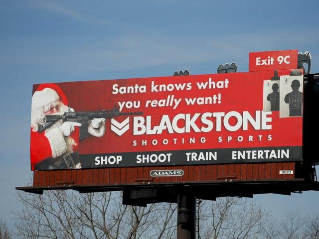 A billboard for Blackstone Shooting Sports showing a man dressed as Santa Claus holding a firearm is seen in Charlotte, North Carolina.