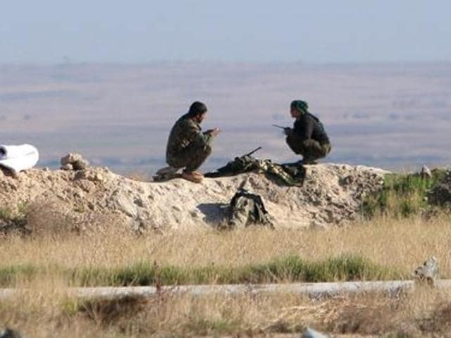 Fighters from the Democratic Forces of Syria sit at one of their guard posts in the 121 Regiment base.