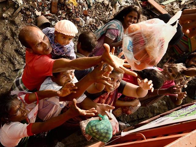 People reach out to collect relief materials being distributed in Chennai. The worst flooding in a century in Tamil Nadu has left scores of people dead since November.