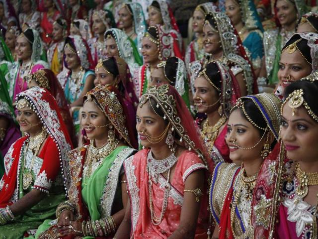 Indian brides sit for a group photo before a mass wedding hosted by a diamond trader in Surat.