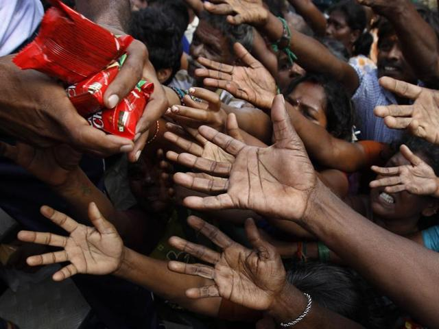 People reach out to collect relief materials being distributed in Chennai.