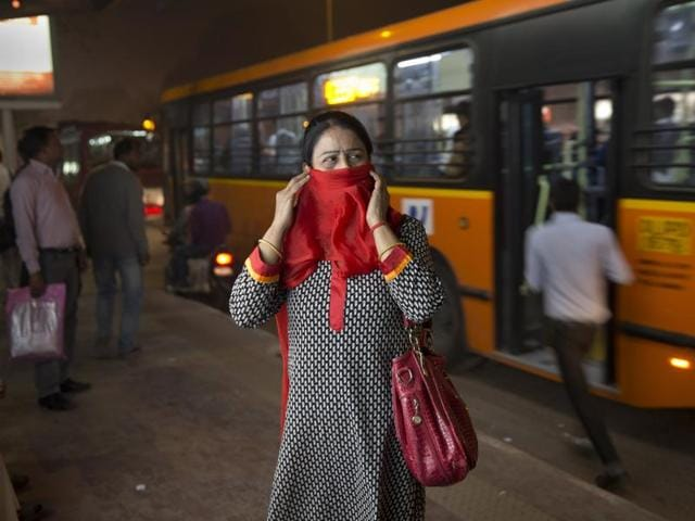 In this November 27, 2015 photo, a woman covers her face from pollution as she waits at a bus station in New Delhi. To discourage private car use, we need to invest in public transport.