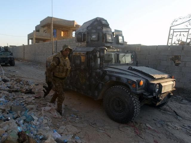 Iraqi troops and allied paramilitaries advance on December 6, 2015 down a street in Husayba, an Iraqi rural town in the Euphrates Valley seven kilometres (4.5 miles) east of Ramadi.