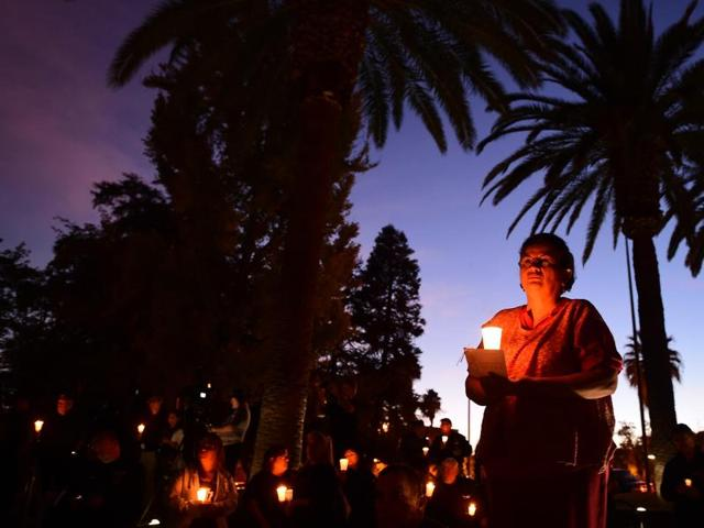 Photographs of victims of the terrorist attack on the Inland Regional Center are seen as people hold candles while attending a vigil held at the San Bernardino County Board of Supervisors headquarters.