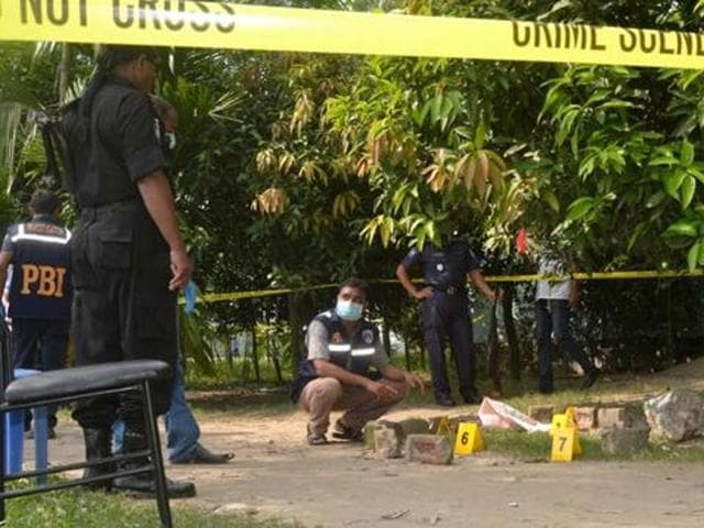 Bangladeshi security officers examine the site where the Japanese citizen Kunio Hoshi was shot dead by masked assailants on a motorbike, at Mahiganj village in Rangpur district, 300 km north of Dhaka.