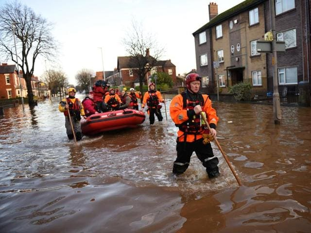 Members of the emergency services walk through flood waters as they prepare to rescue residents from their flooded properties at dusk in Carlisle.