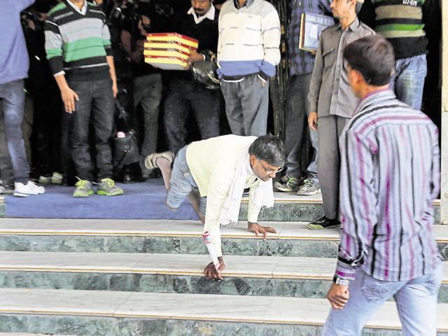 A man with disability stumbles while climbing down the stairs at a felicitation ceremony at Ravindra Manch in Jaipur on Monday.