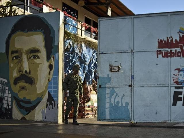 A Venezuelan soldiers walks next to a mural depicting Venezuelan President Nicolas Maduro at the entrance of a school in Caracas, on December 7, 2015.