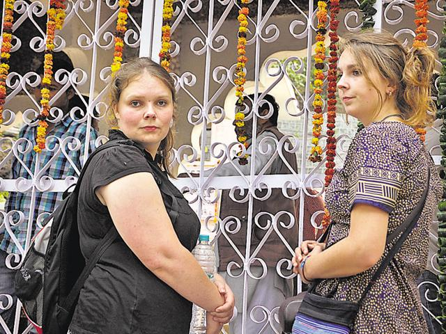 Two foreigners wait at the gate of Beatles Ashram on Tuesday.