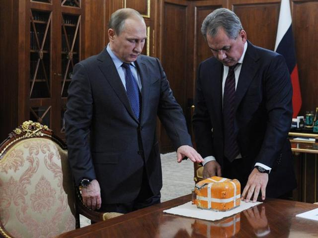 Russian President Vladimir Putin (L) and Defence Minister Sergei Shoigu examine the flight recorder from the Russian Sukhoi Su-24 bomber which was shot down by a Turkish jet.