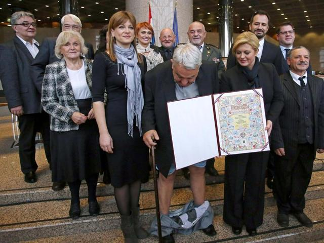 A combination of pictures made on December 8, 2015 shows Croatia's leading rights group chief Ivan Zvonimir Cicak's (L) looking down and pulling up his trousers after they fell down while posing for a photo with Croatian President Kolinda Grabar-Kitarovic (R) on December 8, 2015 in Zagreb.