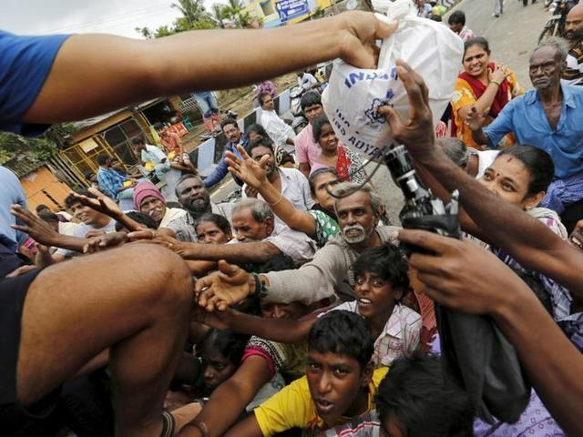 Flood-affected people raise their hands to receive free food being distributed by Indian Navy personnel in Chennai.