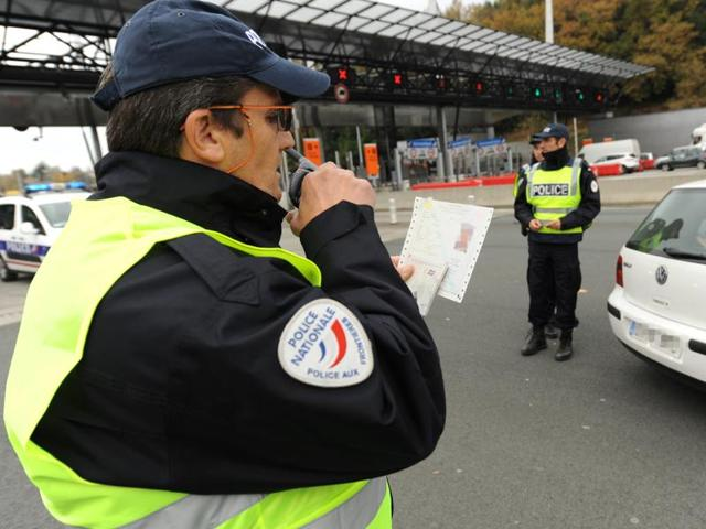 A French police officer checks a man's passport and identification papers at a border post.