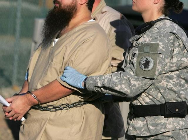 A shackled detainee is transported by a female guard and male guard at Camp Delta detention centre, Guantanamo Bay US Naval Base.