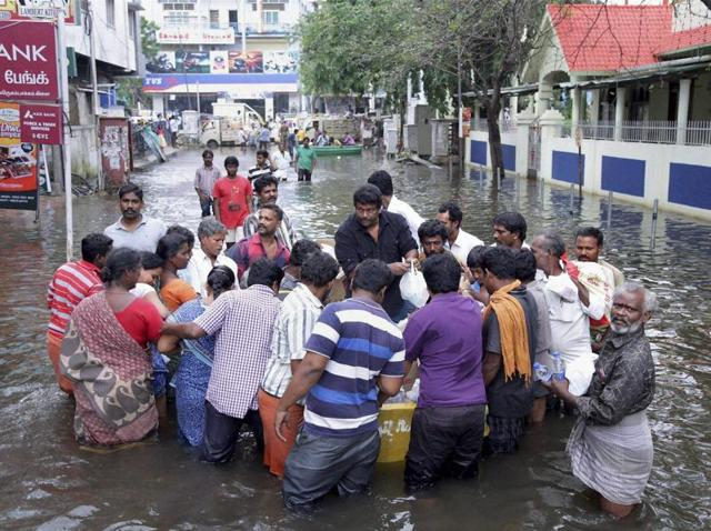 Tamil actor and director Radhakrishnan Parthiban distributes food packets to flood-affected people in Chennai.