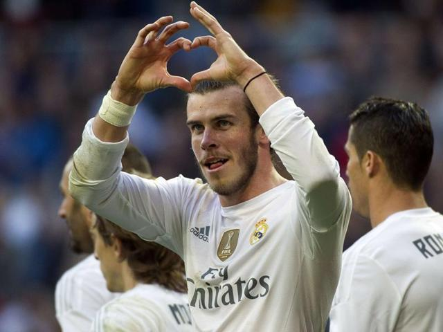 Real Madrid's Welsh forward Gareth Bale gestures as he celebrates a goal during the Spanish league football match Real Madrid CF vs Getafe CF at the Santiago Bernabeu stadium in Madrid on December 5, 2015.