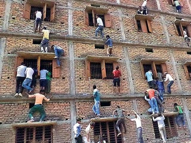 Family members and friends scaling wall of a government school at Mahnar in Bihar's Vaishali district to pass on answer chits to the students appearing in Class 10 exam in March this year.