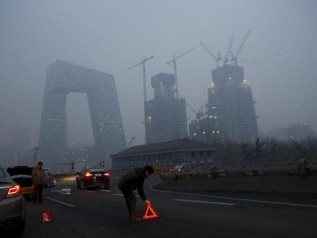 A couple wearing masks make their ways in a shopping district amid heavy smog. The red alert continued in Beijing for a third consecutive day.