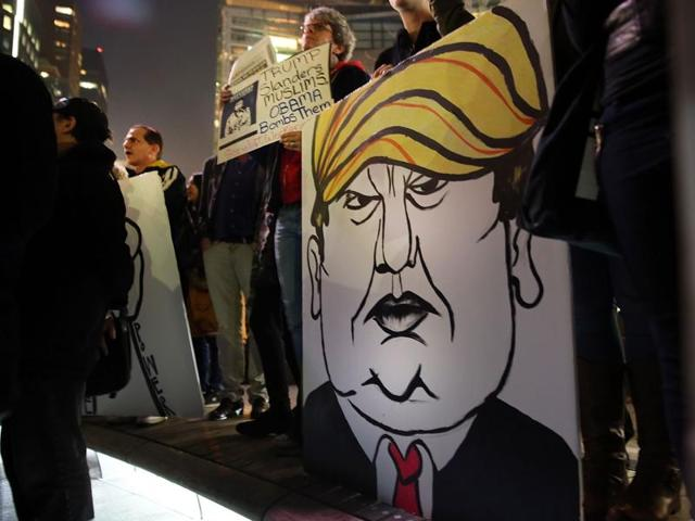A protester holds a caricature of presidential candidate Donald Trump during a demonstration against racism. Trump's recent remarks that Muslims should be banned from entering the US is attracting him much criticism from all fronts.