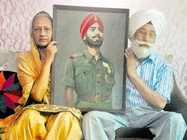 Amarjeet Kaur and her husband Shamsher Singh with Nand Singh's portrait.