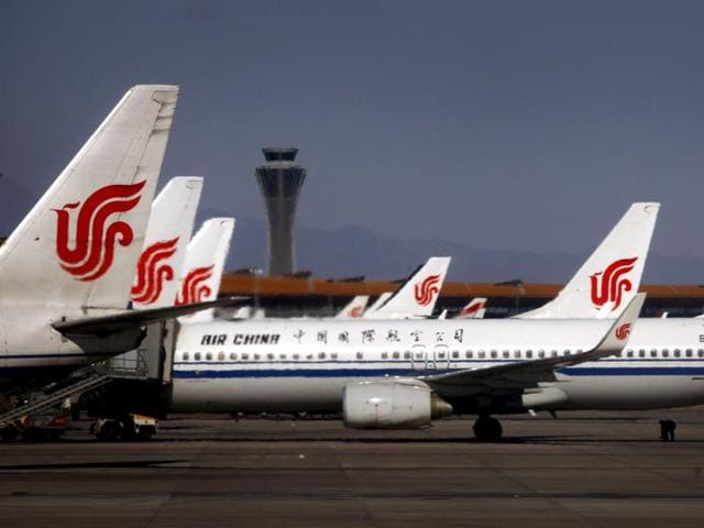 An airport worker inspects the under-carriage of Air China planes while they are parked at the terminal building of Beijing's International Airport in this file photo.