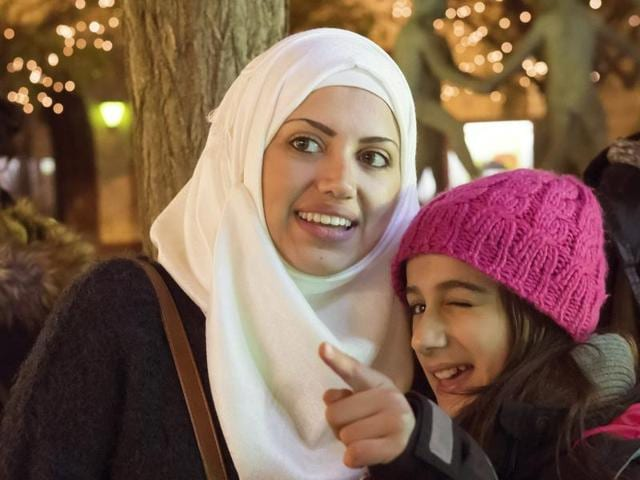 In this photo taken Tuesday, Dec. 8, 2015, Syrian refugee Raghad Habashieh, right, talks with her sister Reem Habashieh, left, as they visit the Christmas market in Zwickau, eastern Germany.