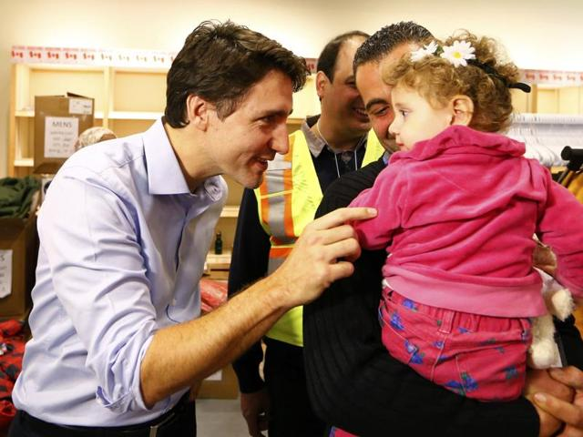 Syrian refugees are greeted by Canada's Prime Minister Justin Trudeau (L) on their arrival from Beirut at the Toronto Pearson International Airport in Mississauga, Ontario, Canada.