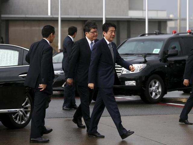 Japan's Prime Minister Shinzo Abe (C) walks as he departs for India at Tokyo's Haneda airport, Japan.