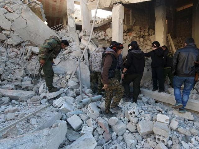 Kurdish fighters from the People's Protection Units (YPG) inspect damage at a site hit by one of the three truck bombs, in the YPG-controlled town of Tel Tamer, Syria.
