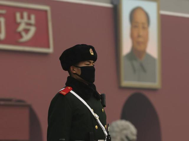 A paramilitary policeman wearing a mask stands guard in front of the giant portrait of Chinese late chairman Mao Zedong, amid heavy smog after the city issued its first ever