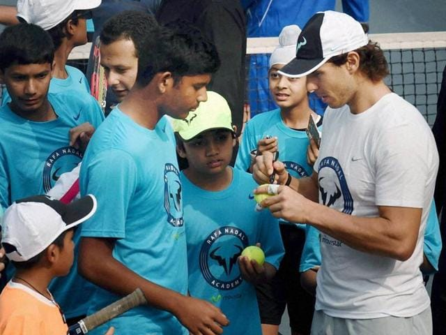 Rafael Nadal is presented with a bouquet by a child at a promotional event in New Delhi, India on December 10,2 015.