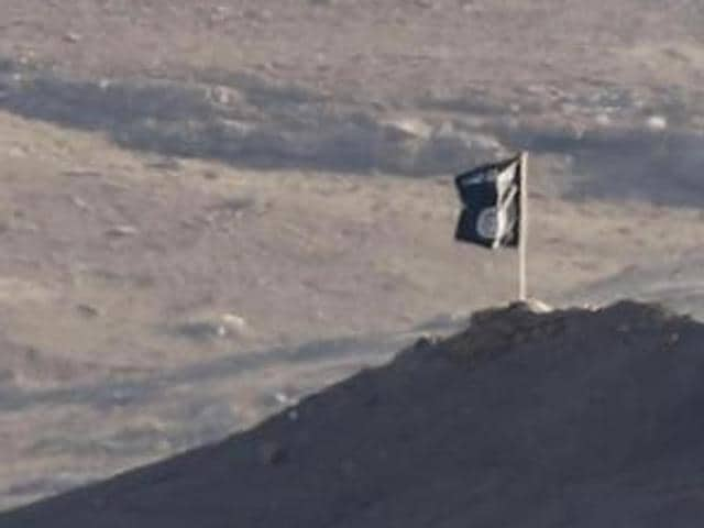 A black flag belonging to the Islamic State is seen near the Syrian town of Kobani, as pictured from the Turkish-Syrian border near the southeastern town of Suruc in Sanliurfa province.