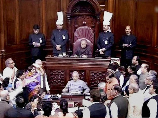 Members protest in the well of Rajya Sabha during the ongoing winter session of Parliament in New Delhi on Thursday.