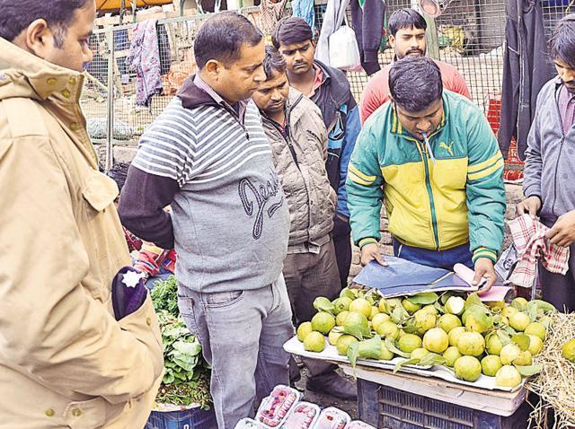 Officials issuing challans after discovering vendors using plastic bags in Sector 26 , Chandigarh.