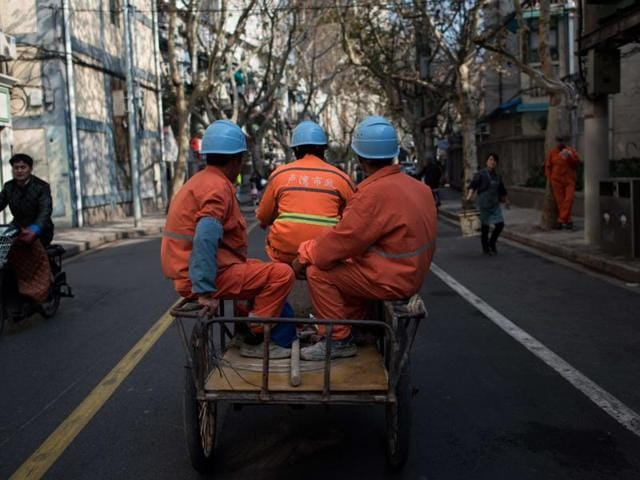 Workers ride on their tricycle along a road in downtown Shanghai.