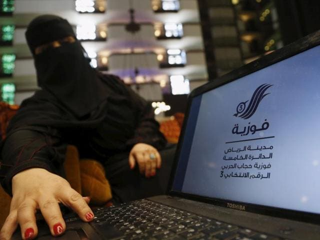 Saudi woman Fawzia al-Harbi, a candidate for local municipal council elections, shows her candidate biography at a shopping mall in Riyadh. Saudi Arabian women are running for election and voting for the first time on December 12, but their enfranchisement marks only a pigeon step towards democracy and gender equality in the autocratic Islamic kingdom.