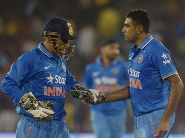 India's captain Mahendra Singh Dhoni congratulates Ravichandran Ashwin for taking a wicket during the second T20 cricket match between India and South Africa at The Barabati Stadium in Cuttack on October 5, 2015.