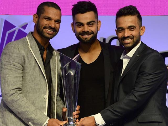 Indian cricketers Shikhar Dhawan, Virat Kohli and Ajinkya Rahane smile while posing with the ICC World Twenty20 India 2016 trophy during an event to announce the groups and schedule in Mumbai on December 11, 2015.