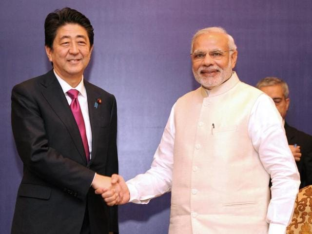 In this handout photograph released by PIB, Prime Minister Narendra Modi (R) shakes hands with Japan's Prime Minister Shinzo Abe ahead of a meeting at a business forum in New Delhi.