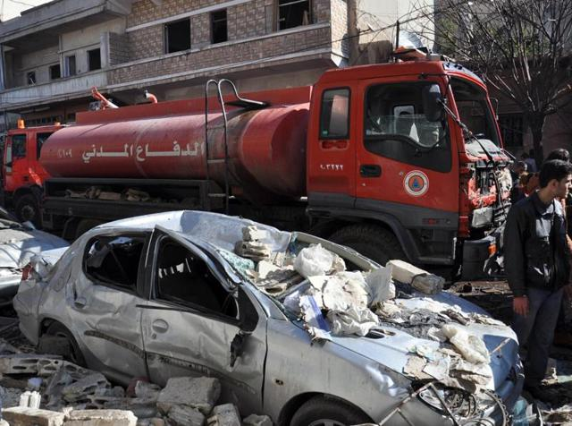 A firefighter truck is seen next to a destroyed car at the site of a car bomb explosion in al-Zahra neighborhood in Homs.