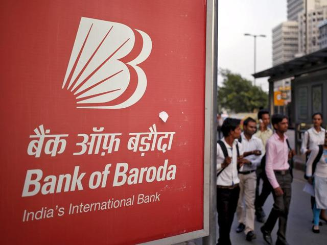 Commuters walk past an advertisement of Bank of Baroda, India's second-biggest state-owned bank in New Delhi.