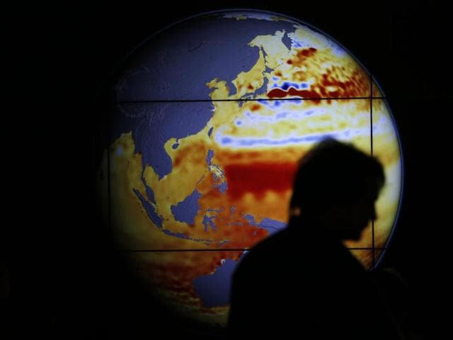 A woman walks past a map showing the elevation of the sea in the last 22 years, during the World Climate Change Conference 2015 (COP21) at Le Bourget, near Paris, France.
