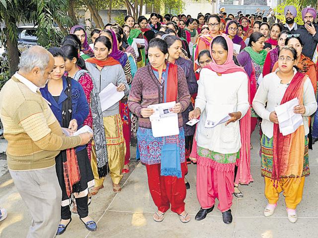 District education officials checking documents of Punjab State Teacher Eligibility Test (PSTET) candidates outside the examination centre in Amritsar on Sunday.