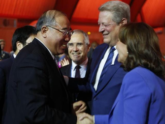French President Francois Hollande (C) embraces Christiana Figueres, Executive Secretary of the UN Framework Convention on Climate Change, as United Nations Secretary-General Ban Ki-moon (R) looks on at the final plenary session at the World Climate Change Conference 2015 (COP21) at Le Bourget, near Paris, France, December 12, 2015.