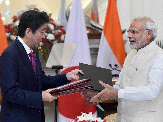 Prime Minister Narendra Modi (R) shakes hands with Japan's Prime Minister Shinzo Abe at Hyderabad House in New Delhi on December 12, 2015.