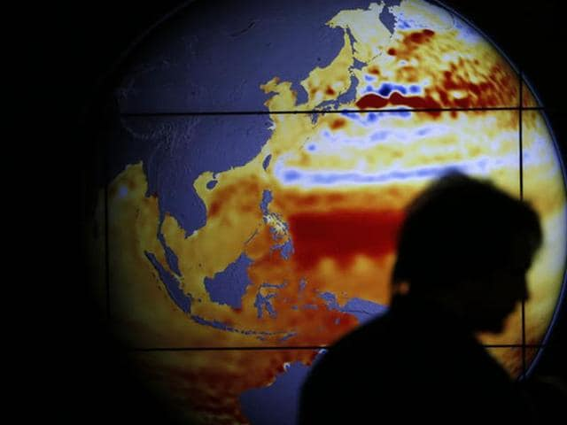 A woman walks past a map showing the elevation of the sea in the last 22 years during the World Climate Change Conference.
