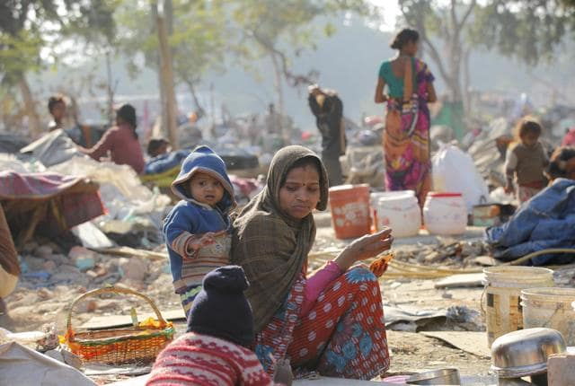 A woman sits near her demolished shanty after an anti-encroachment drive conducted by the Indian Railways razed hundreds of shanties.